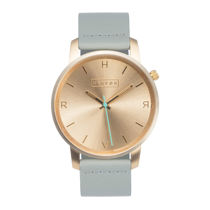 All gold Hervor watch with dove grey leather strap and a turquoise accent second hand