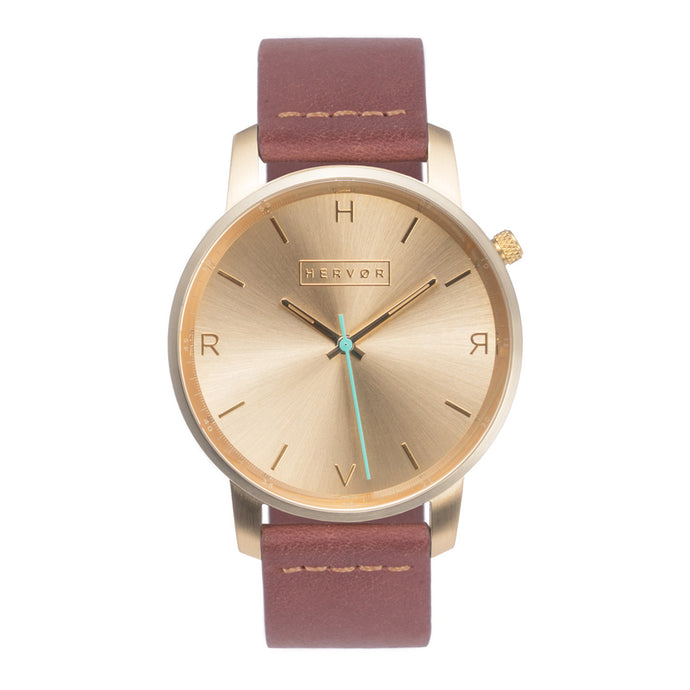 All gold Hervor watch with dusty rose dark pink leather strap and a turquoise accent second hand