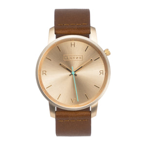 All gold Hervor watch with fox brown leather strap and a turquoise accent second hand