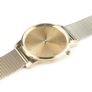 All gold Hervor watch with gold metallic mesh strap and a turquoise accent second hand