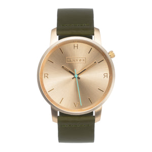 All gold Hervor watch with olive khaki green leather strap and a turquoise accent second hand