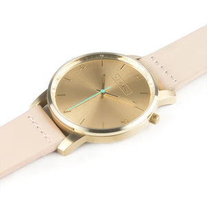 All gold Hervor watch with light pink skin tone leather strap and a turquoise accent second hand