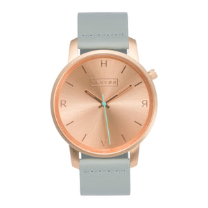 All rose gold Hervor watch with dove grey leather strap and a turquoise accent second hand