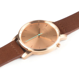 All rose gold Hervor watch with fox brown leather strap and a turquoise accent second hand