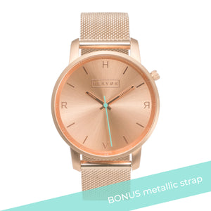 All rose gold Hervor watch with rose gold metallic mesh strap and a turquoise accent second hand