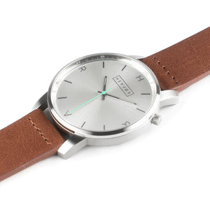 All silver Hervor watch with fox brown leather strap and a turquoise accent second hand
