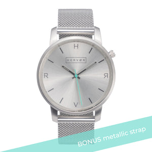 All silver Hervor watch with silver metallic mesh strap and a turquoise accent second hand