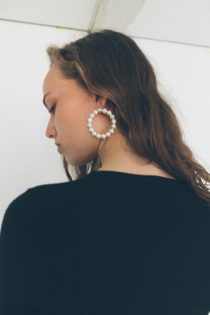 Two hoops earrings from Mirit Weinstock, each hoop is fifteen fresh water shell coating syntactic pearls white color and two silver sterling beads