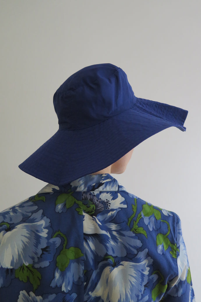 Vintage Blue wide brim bucket hat in Gore-Tex, a waterproof and breathable fabric, featuring an adjustable string