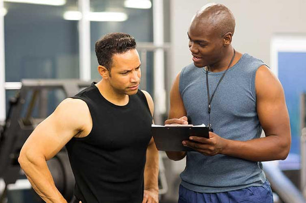 Fitness Training Provider gives instruction at gym to fitness student