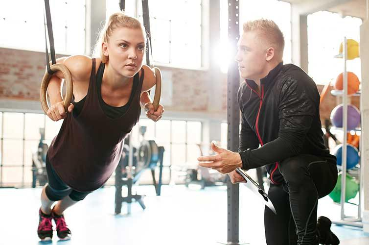 Personal Trainer gives advice to student at Fitness Training gym
