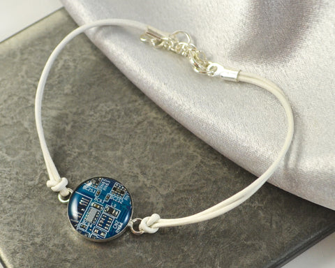blue circuit board and white leather bracelet