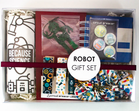handmade gift set with recycled circuit board robot ornament, robot scrunchie, robot pins, because science tea towel, floppy disc notebook, and robot themed magnetic clip set