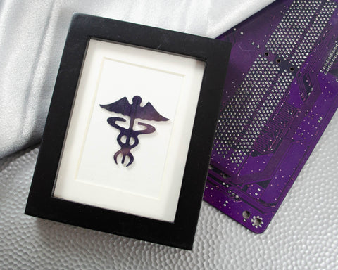 custom framed circuit board art of the caduceus. it's the perfect just because gift or a holiday secret santa gift for your favorite nurse. It's handmade in washington DC using electronic waste. Get in touch if you'd like to personalize your own custom art piece