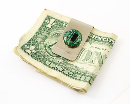 green circuit board money clip holding dollar bill