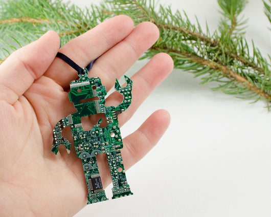 green circuit board ornament robot shape held in hand with evergreen