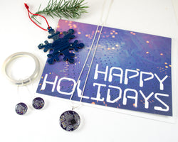 happy holidays gift set with necklace, earrings, snowflake ornament, and greeting card