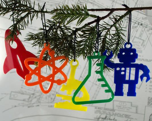 set of rainbow scrylic science ornaments including rocket, robot, erlenmeyer flask, microscope, and atom