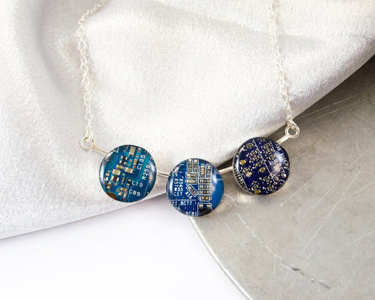 three different shades of blue circuit board made into a hand fabricated sterling silver necklace
