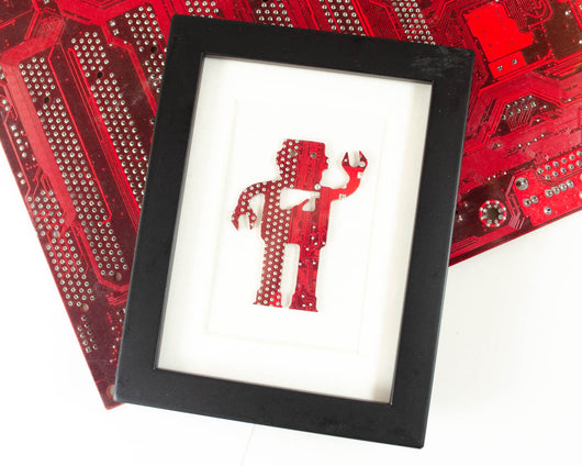 robot made from recycled red circuit board in black frame