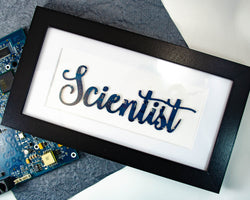 handmade framed art piece with scientist written in a hand lettered style made from recycled circuit board