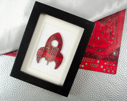 handmade framed artwork of a stylized rocket ship made from recycled red circuit board