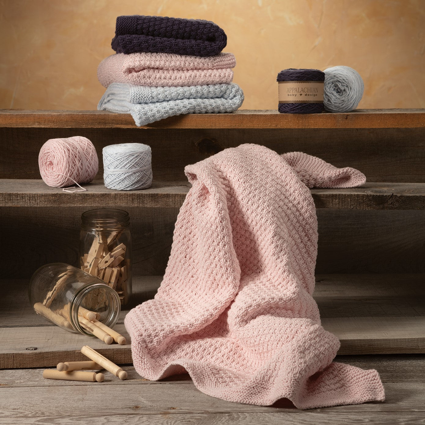 Soft pink textured-knit baby blanket draped on rustic 3-shelf bookcase with old-fashioned clothes pegs spilling from a glass jar on the bottom shelf and three baby blankets of the same pattern in blue, ecru, and pink folded on the top shelf.
