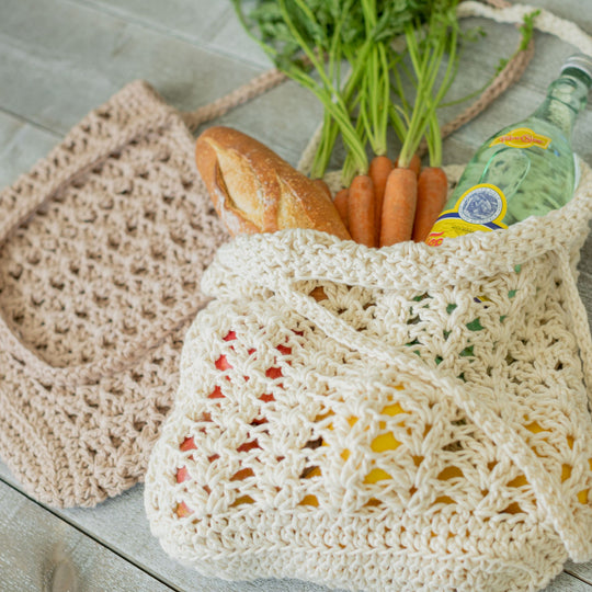 Two crocheted string bags, one beige and one ecru, laying on a tile surface. The beige bag is empty and flat. The ecru bag holds a bunch of carrots, a baguette, and a glass bottle that appears to be mineral water sticking out the top, with red and yellow visible through the inside - probably tomatoes and lemons