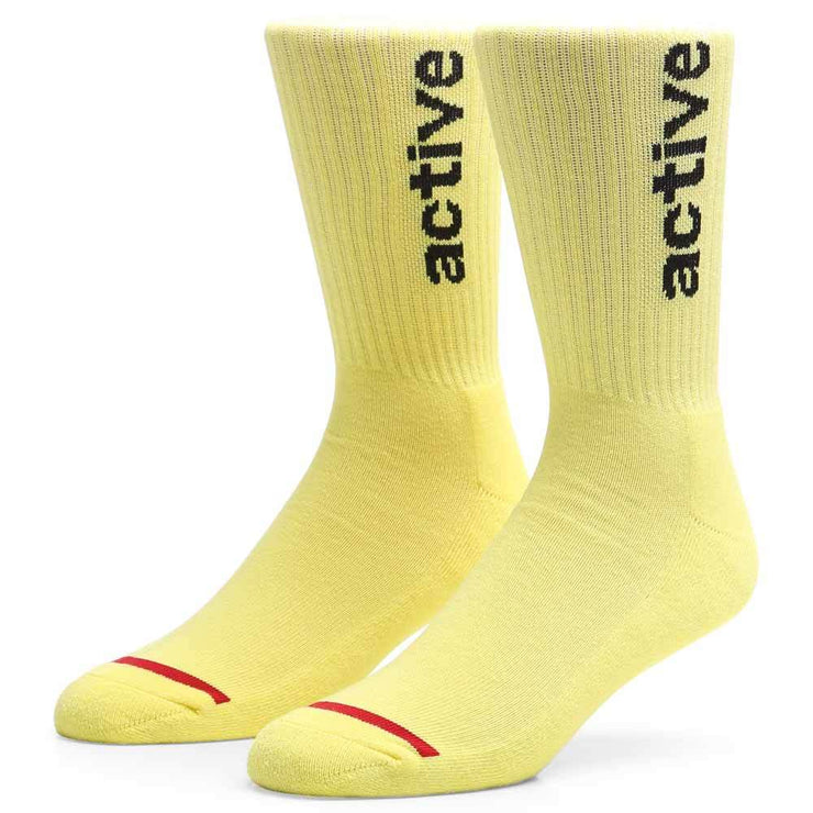 "Active Ride Shop Men's Crew Socks in Pastel Yellow with black ""active"" writing up the side."
