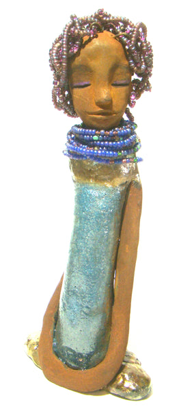"Clarice stands  11"" x 5"" x 3.5"" and weighs  1.14 lbs.     . She has a yellow brown complexion with small purple beaded hair. Clarice's dress is a light blue crackle. She wears a blue beaded collar."