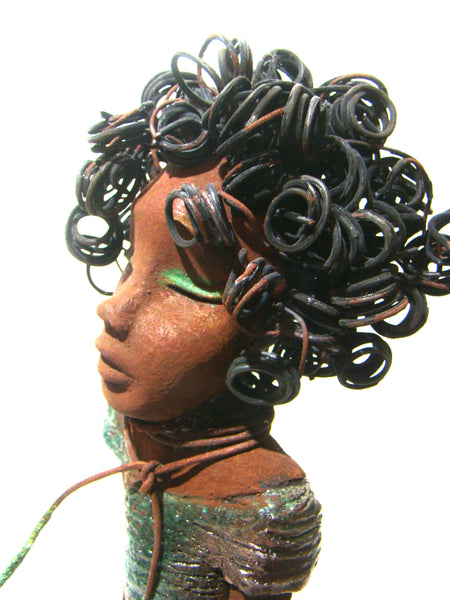 "Kylie stands 14"" x 7"" x 3"" and weighs 3.03 lbs. She has a textured copper green dress with a brown seude cord necklace. Kylie has a honey brown complexion with long loving arms. Kylie has over 20 feet of 16 gauge curly wire hair!"