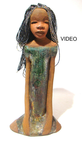 "Michelle stands 18"" x 9"" x 4.5"" and weighs 5.14 lbs.     Michelle has a metallic alligator green dress with hints of shimmering copper.     She has a lovely two tone honey brown complexion.     Michelle has her long loving arms resting at her side.     Why not give Michelle a special place in your home!"
