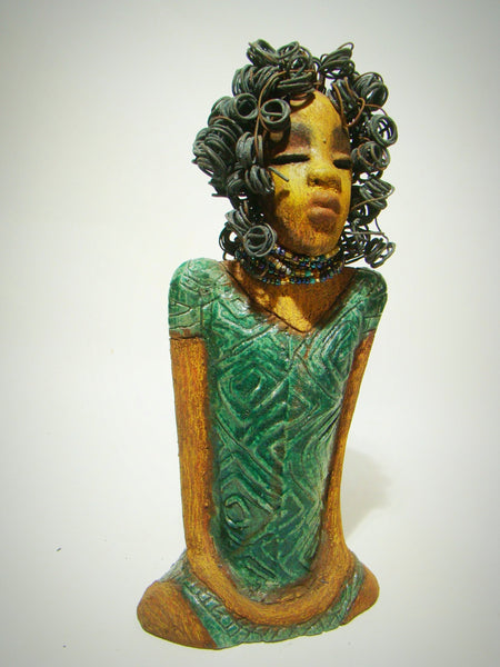 "Shirley is approx. 13""x 7""x 5"" and  weighs approx. 5 pounds. Her long loving arms rest at her knees. Shirley has honey rust colored complexion and wears copper glittery eye shadow. Her dress is glossy copper green.  A string of multi colored beads wrap snugly around her neck."
