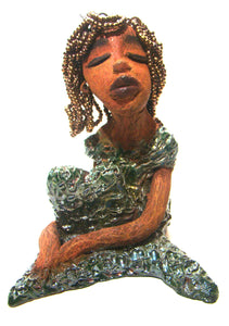 "Mabel sits 7"" x 5"" x 5"" and weighs 1.8 lbs.     Mabel has her arms wrapped around her legs with her knees up.     She has amber beaded hair with a lovely honey brown complexion.     Yes Mabel is a raku fired Mermaid."