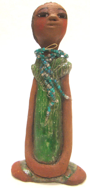 "Fatou stands 9"" x 4.5"" x 2"" and weighs 1.03 lbs.     She has a lovely honey brown complexion and long loving arms.     Fatou has an emerald glazed dress with a strand of multicolored beads.     Her hair is raku smokey black and is etched in clay.     Fatou is eye catching and will grace your surroundings."