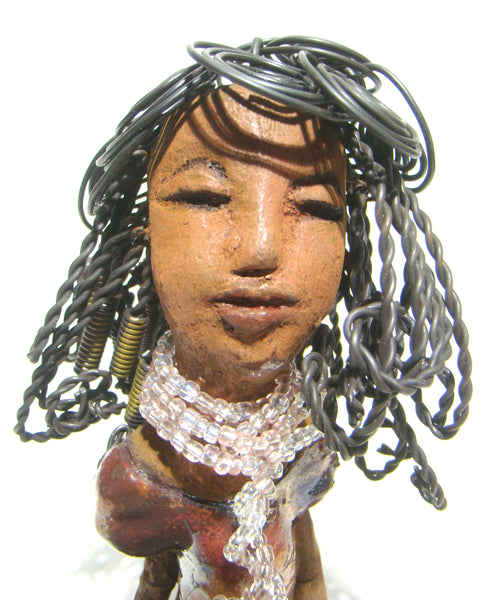 "Geneva is a cutie!      She stands 8"" 4"" 3"" and weighs 1.5 lbs.     Geneva has a honey brown complexion with twist, curls, and coiled hair.     She wears off white and clear beads as a collar  to accentuates her multi colored metallic copper dress."