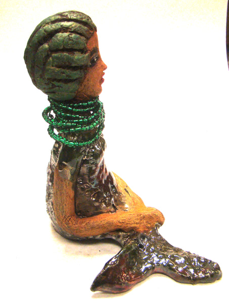 "Meet Julie!      Julie the Mermaid stands 7"" x 4"" x  5"" and weighs 2 lbs.     Julie has a honey brown complexion with golden green clay hair.     Her long loving arms rest in her lap.     She wears a glossy copper metallic swimsuit.     Julie sports a long hanging emerald  beaded necklace.     Give Julie a special place in your home!  Free Shipping!"