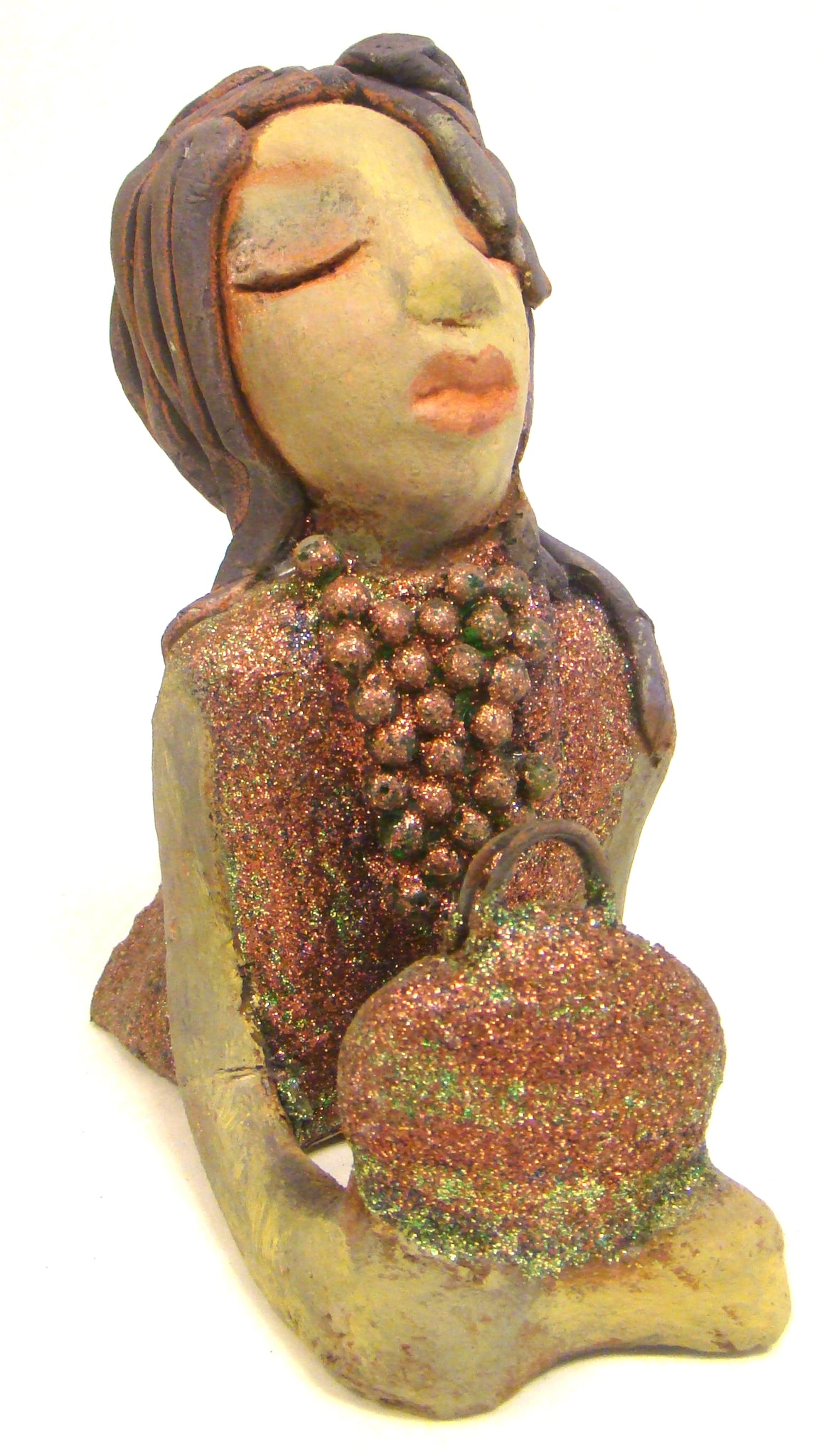 "Lacey stands 6"" x 3"" x 7.5"" and weighs 1.08 lbs. She has a lovely beige olive green complexions with ruby red lips. Her hair is made of coiled clay. Lacey is holding her handbag which matches her copper glittered dress. Give Lacey a special place in your home."