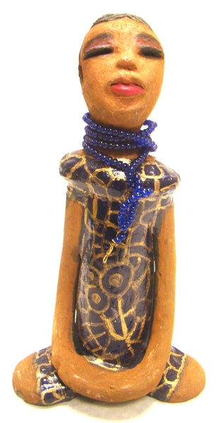 "Meet Latifa!      The name Latifa refers to one that is gentle or pleasant.     Latifa stands 9"" x 5"" x 3"" and weighs 1.04 lbs.     She has a lovely honey brown complexion.     Her long loving arms rest at her side.     Latifa wears a blue dress with gold spirals.     A strand of blue beads accents her dress.     Latifa hair is etched smokey black clay.     Give Latifa a special space in your home!"