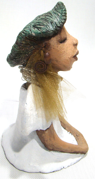 "Nora James stands 8.5"" x 4.5"" x 5"" and weighs 2.03 lbs.     She has a lovely honey brown complexion.     Nora James long loving arms rest at her side.     She wears a matte white dress with a metallic alligator green hat.     Nora James also sports a multicolored beaded necklace with a gold tulle.     Nora James is one of the first small sculptures to be released in 2019!     Free Shipping!"