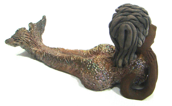 "Meet Belinda!      Belinda is a voluptuous mermaid.     She stands 6.5"" X 5"" 9.5"" and weighs 2.04 lbs.     Belinda has a dark chocolate complexion.     She wears a  dark smokey clay hairstyle.     She wears a glossy metallic swimsuit.     Belinda has a wide tail.     She will  definitely get somebody's attention."