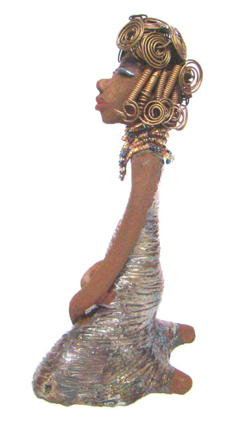 "Gloria  is a raku fired and stands 12"" x 7"" x 5"" and weighs 2.1lbs. She has a lovely brown complexion. Gloria's hair is gold and black. It took over 3 hours and 40 feet of coils and spiral 16 guage wire to complete."