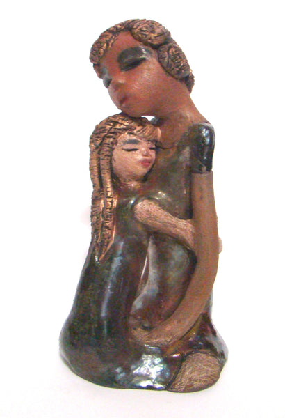 "Hold Me Mama depicts the bond between a mother and child. They stand 10"" x 5"" x 5"" and weighs 2.8 lbs. Mother and Child has honey brown complexions with etched..."