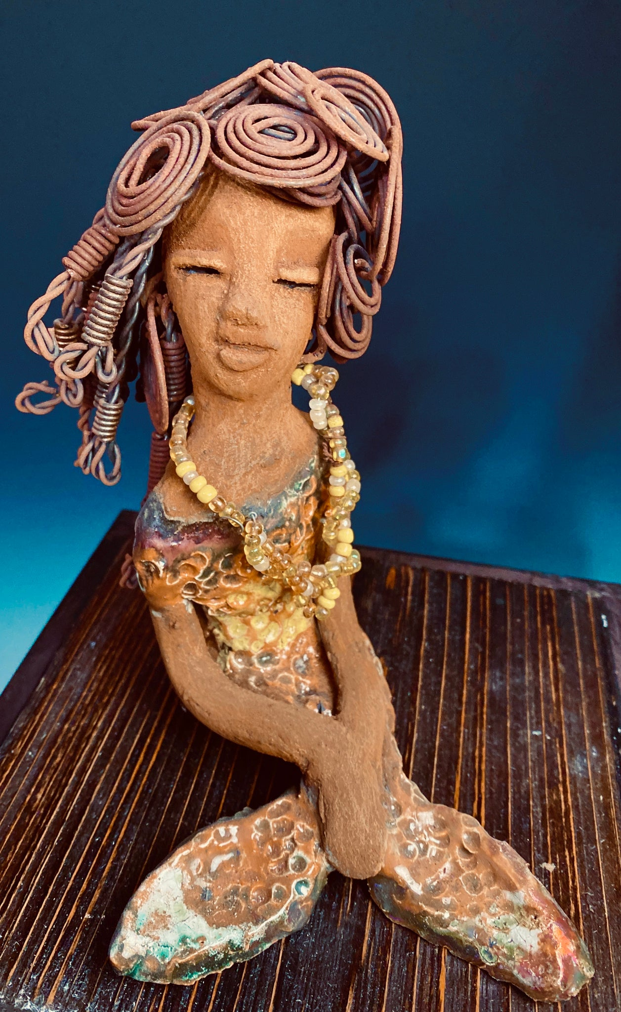 "Meet Isabella the Mermaid! Isabella stands 7' x 4"" x 6"" and weighs 1.08 lbs.. Isabella  has a lovely brown complexion. Her long loving arms are crossed in her lap. Isabella has over 20 feet of  wire hair. It took over two hours to fix her hair! Isabella has a metallic yellow swimsuit with flashes of copper. She wears a yellow beaded necklace. Isabella appears to have something on her mind! Give Isabella a special space in your home!"
