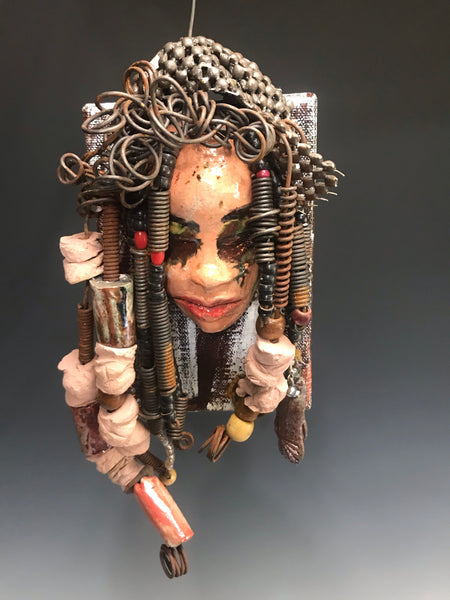 "Kamara is uniquely mounted on a painted 6""x 4""x 2"" canvas. It weighs 1.6lbs.     Her face is formed with hand coiled wire, raku beads, textured brown cloth, and multi color raku beads.     Kamara's face beams with pale pink crackle glaze and ruby red lips.  Kamara is ready to be hung in a special place!"