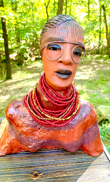 "Meet Harriet! Harriet stands 13"" x 11"" x 5"" and weighs 5 lbs. She wears a coral striped dress with a string of ruby red and gold beads. Harriet has a honey brown rust complexion  and distinct eyes. Her eyes  are slightly opened underneath her glasses... She has mixed black and copper streaks of straight corn rolls of clay hair. She has a straight look of concern as to what is about to take place."