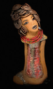 "Meet Kate! Kate stands 10' x 5' x 3"" and weighs 1.12 lbs. She has a nice golden brown complexion. Kate has a head full of wire hair that took over 3 hours style! Her dress is made with a glossy metallic red and gold glaze. She has her long loving arms at her side. Kate head is slightly tilted  with curiosity! Kate reminds a little of her cousin Sandra. Give Kate an interesting place to showcase in your home."