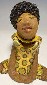 "Meet Shelia! Shelia stands"" 5 x 4"" x 3"" and weighs 11 ozs. She wears a cute spotted autumn yellow dress with matching beads. She has a lovely honey brown complexion with an awesome black afro.. Her long loving arms rest at her side. With the current situation we All are going through, Shelia will place a smile on your face during this challenging time."