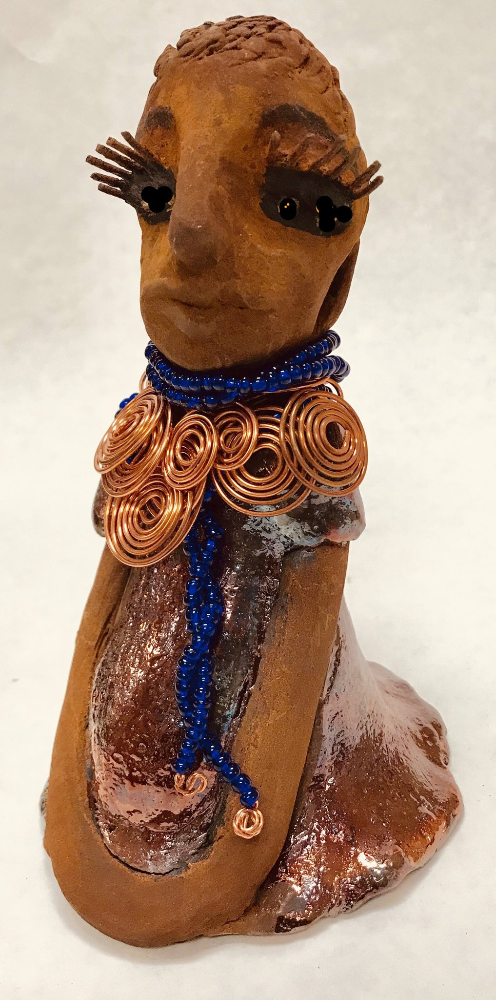 "Tattayana stands 8"" x 4.5"" x 5"" and weighs 1.02  lbs. She has a lovely honey brown complexion with reddish brTattayanaown lips. She has a short braided hairstyle.  Tattayana has a colorful metallic antique copper glazed dress. She wears spiral copper wire necklaces on top of an aqua blue beaded collar.  Tattayana has her long loving arms rest at her side. With eyes wide opened,Tattayana  has hopes of finding a new home."