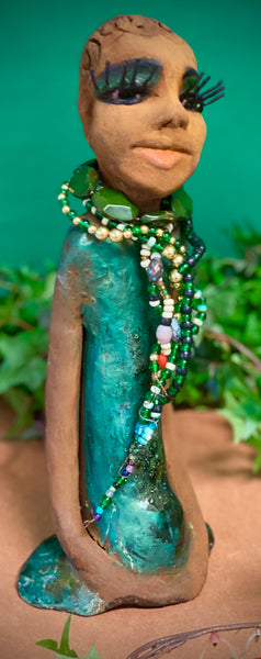 "Meet Makeda  What a joy to be around Makeda! She is one of many who has a polite gentle spirit! Makeda 12"" x 6"" x 4"" and weighs 1.1 lbs. Makeda has a lovely honey brown complexion. Her  hair is made of textured clay. She has a  copper green metallic dress. Makeda Is a a young  lady full of pride and joy."